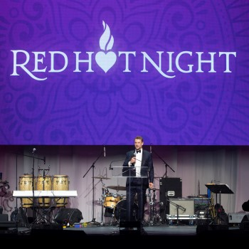 """Man on stage with microphone and the words """"Red Hot Night"""" above him."""