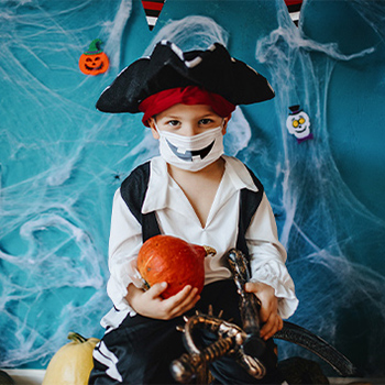 A child dressed as a pirate for Halloween with a white face mask that has black jack-o-lantern teeth