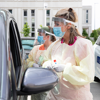 Two nurses in PPE at a car for COVID-19 testing.