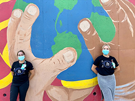 Abby Kietzman and Shannon Hill, RN, BSN wearing facemasks and standing outside, in front of a mural with three hands holding the planet Earth.