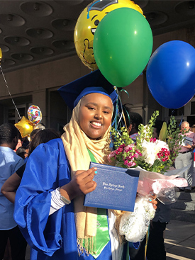 Munira Nuru smiling while wearing a graduation cap and gown, and holding her diploma, flowers and balloons.
