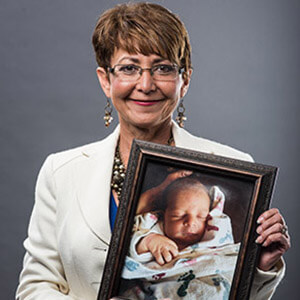 Vicky Clarke holding a framed photo of a baby