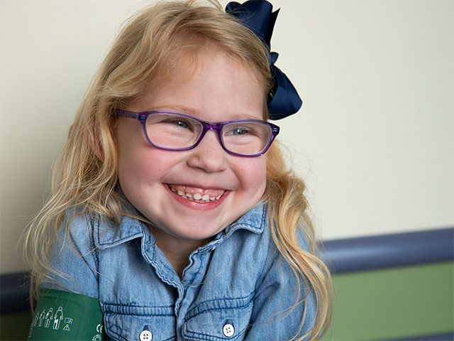 Little girl with glasses smiling.