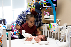Baby Jaciel being visited by his younger brother and father at Children's Mercy.