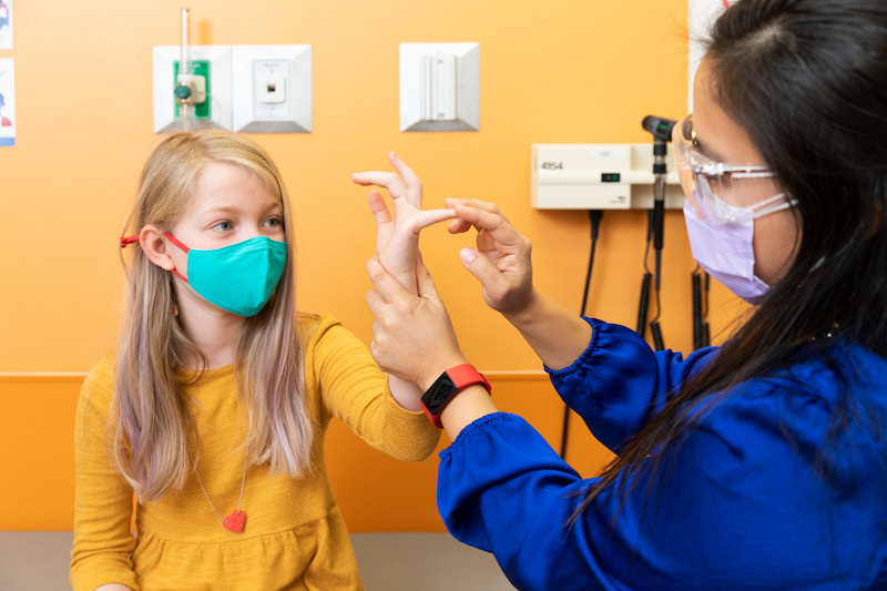 A female clinician bends the finger of a female patient during a physical exam at the Children's Mercy Genetics Clinic.