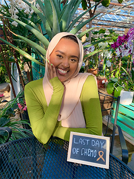 """Munira  Nuru smiling and sitting in back of a sign that reads, """"Last day of chemo."""""""