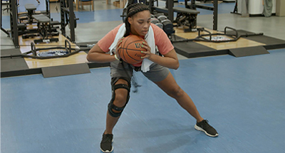 Physical therapy patient doing lateral stretch with basketball in her hands
