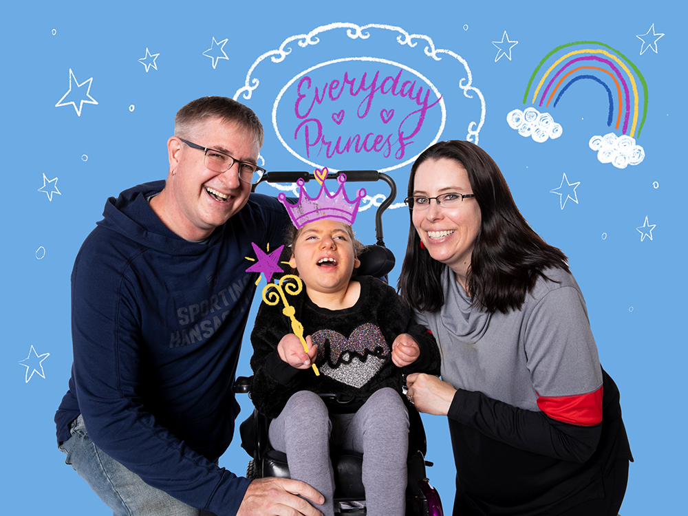 """Hudsyn, a patient with complex medical needs, with her parents. She's holding an illustrated wand and she's wearing an illustrated crown. Light blue background with stars, a rainbow, and """"Everyday princess."""""""