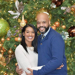 Brandy Dillingham hugging her husband and smiling in front of a decorated Christmas tree.