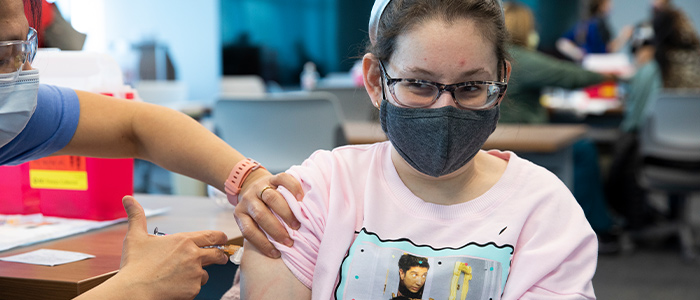 A pre-teen girl wearing a facemask is receiving a COVID-19 vaccination shot at Children's Mercy.