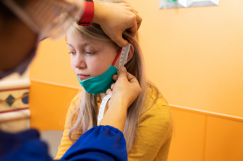 A clinician measures the side of a female patient's face at the Children's Mercy Genetics Clinic.