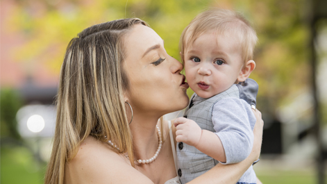 Holden's mother holding him and kissing his cheek