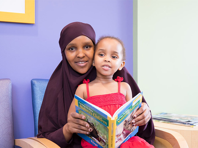 Mother wearing a dark head scarf with her daughter on her lap. The daughter is holding a book open.