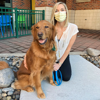 Hunter with handler Aimee Hoflander. Aimee is wearing a face mask and kneeling outside Children's Mercy with Hunter by her side.
