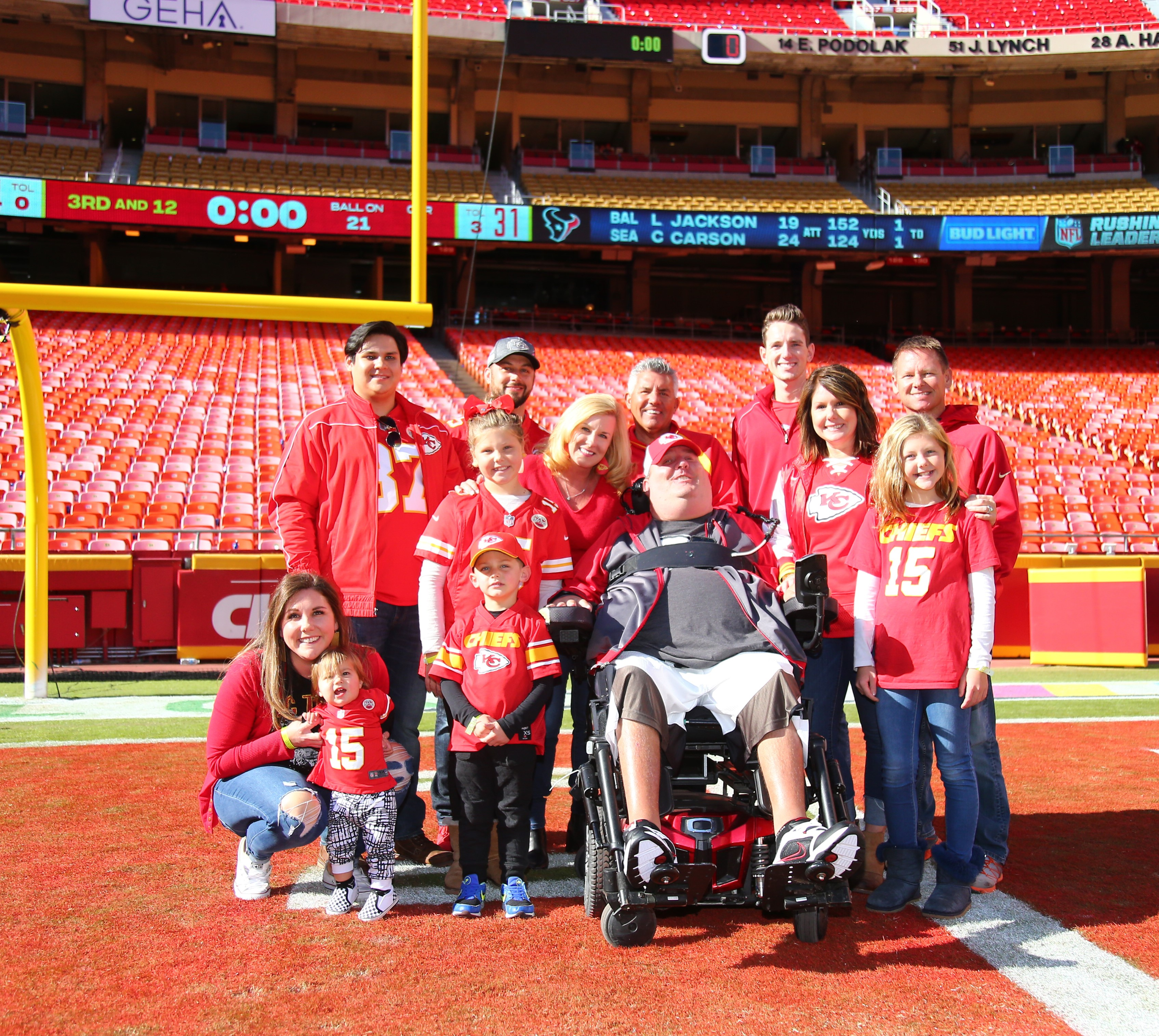 The Baier family (13 people) on the football field at Arrowhead Stadium. They are smiling and wearing red Kansas City Chiefs shirts.