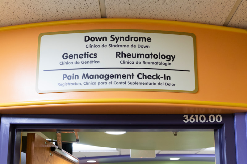 A sign welcomes you to the Children's Mercy Genetics Clinic. Other clinics include Down Syndrome, Rheumatology, Pain Management Check-in.