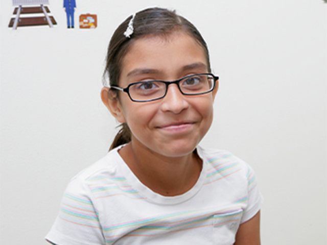 Pre-teen girl with glasses smiling.