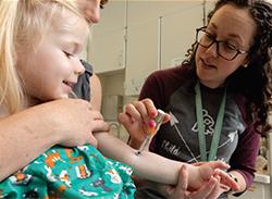 Se usa una punta en J para aplicar un medicamento anestésico en el brazo de un niño.