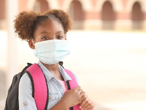 Girl in face mask with backpack