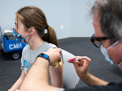 Health care provider giving a teen the COVID-19 vaccination shot.