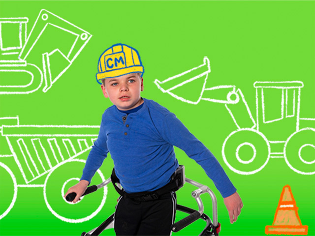 Boy with a walker wearing an illustrated construction hard hat with illustrated construction vehicles in the background.