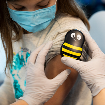 A Buzzy® bee being applied to a child's arm.