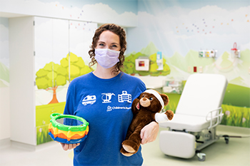 Lenore Flemming is inside a Children's Mercy patient room. She is wearing a face mask and holding a bandaged teddy bear in one hand and a toy in her other hand.