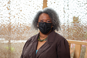 Melva Brownlee is sitting outside the chapel at Children's Mercy wearing a black face mask and smiling with her eyes.
