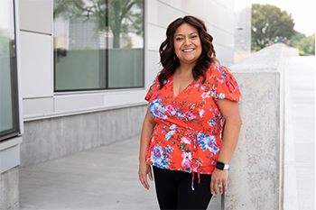 Sylvia Hernandez is smiling and standing outside of the Children's Mercy Research Institute.