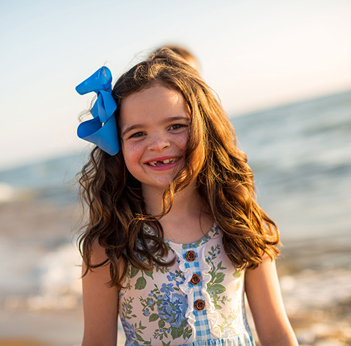Little girl with blue ribbon in her hair smiling on the beach
