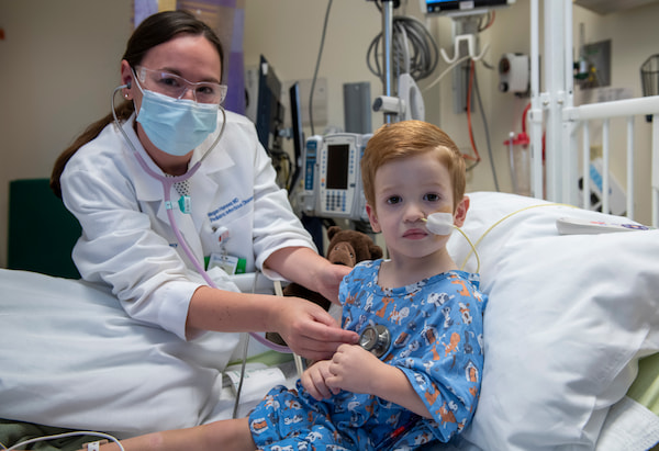 A female physician uses a stethoscope on a young male child who has a feeding tube.