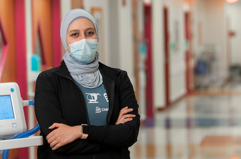 A woman wearing a hijab and a surgical mask stands with arms crossed in a hospital hallway.