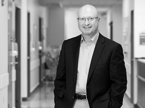 Black and white photo of CEO Paul Kempinski in Children's Mercy hallway smiling.