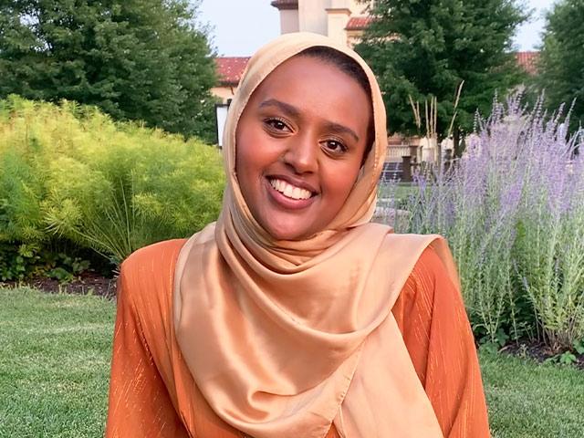 Munira Nura wearing a hijab and smiling.