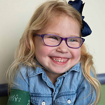 Little girl wearing eyeglasses and a big smile.