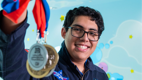 Teo smiling and holding medals