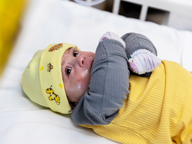 Baby Jaciel Ceballas Lemus laying in a crib, wearing a yellow and gray outfit, and his hands are bandaged.