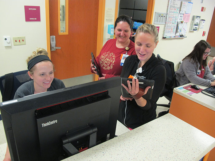 Three Children's Mercy providers looking at computers and smiling.