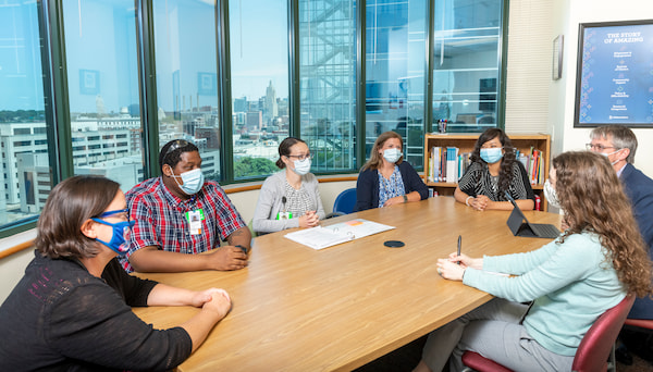 Several masked medical professionals sit at a conference table.