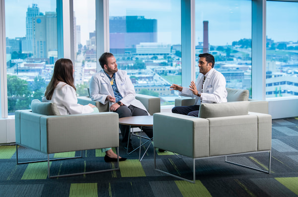 Three physicians, two male and one female, sit and chat next to a window overlooking Kansas City.