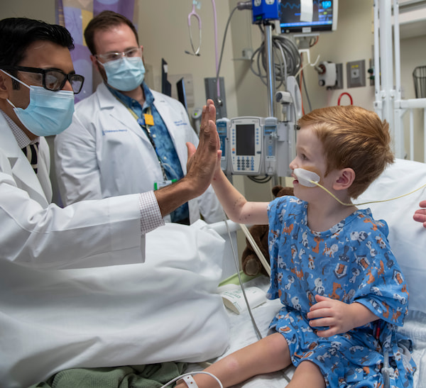 A physician high fives a young male child who is sitting in a hospital bed and has a feeding tube.