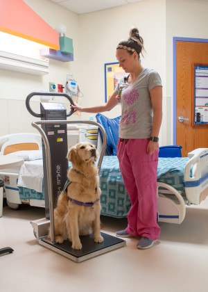 Hope stands on a scale in the EMU at Children's Mercy.