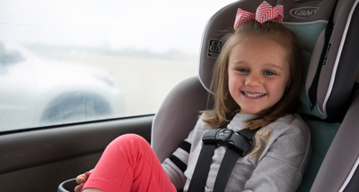 A child smiles in a car seat for the Center for Childhood Safety at Children's Mercy.