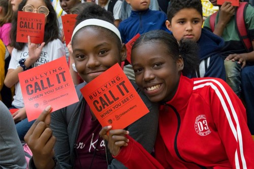 Two school girls holding Red Card anti-bullying cards