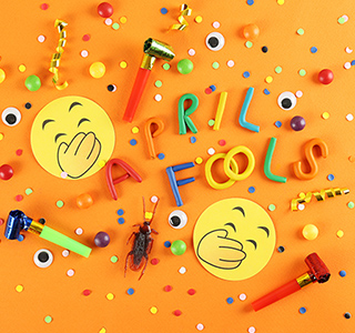 Confetti, laughing emojis, party horns and a fake bug spread out on a table with April Fools text.