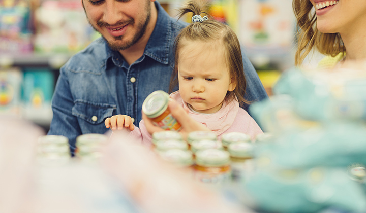 Family with young baby holding baby food jar in a grocery store.
