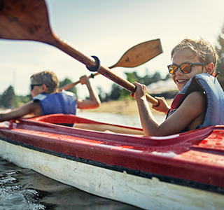 Two young boys in a canoe and wearing life jackets. They are using rowing paddles on a lake and smiling.