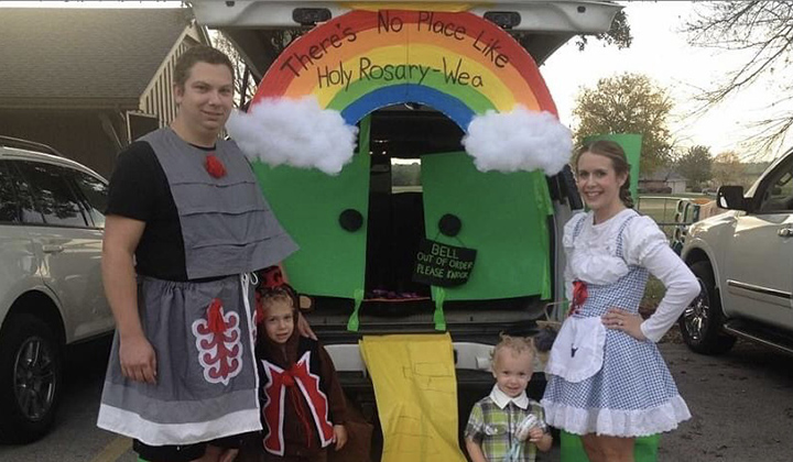 Emily Mccarty, husband and two sons stand at their decorated trunk or treat as Wizard of Oz characters for Halloween.