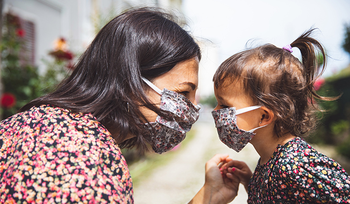 Mom wears a face mask and leans in close to child wearing a face mask.