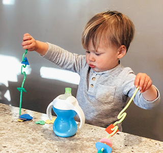 Toddler playing with cups and straws